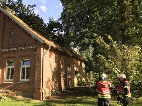 Ein großer Ast einer Eiche auf einem Hausdach in Fredenbeck